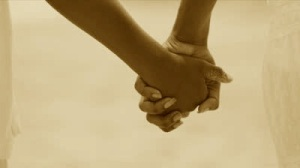 stock-footage-close-up-of-ethnic-hands-holding-walking-on-beach